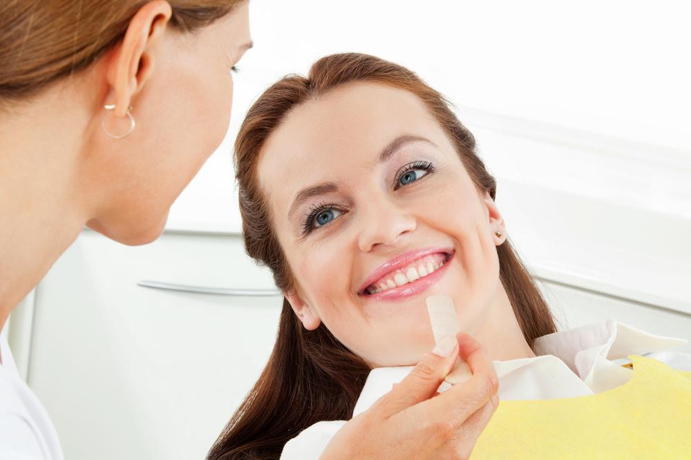 Zahnbrücken: Lächelnde Patientin beim Zahnarzt